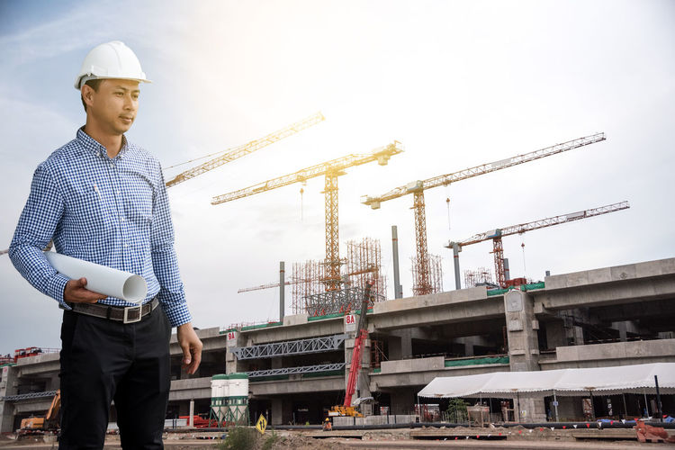 Confident Architect With Blueprint Standing At Construction Site