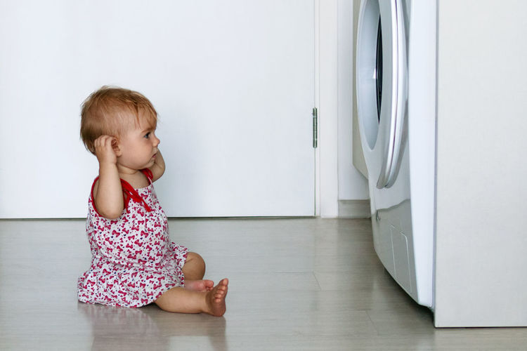 Side view of cute girl sitting by washing machine