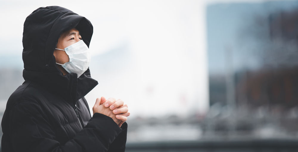 Man with hands clasped wearing mask in city