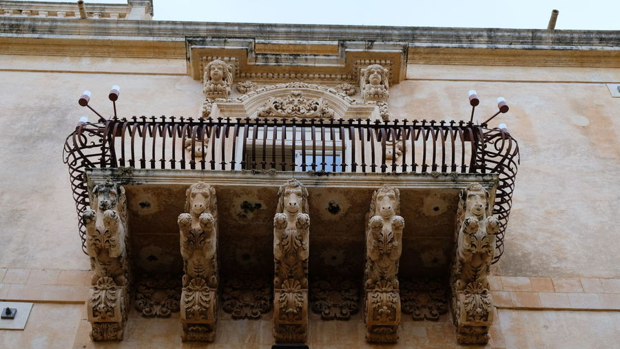 City of Noto. Province of Syracuse, Sicily. One of the spectacular balconies of the Palazzo Nicolaci. The entire city of Noto is known as one of the most remarcable examples of the sicilian baroque style. Noto,sicily Syracuse  Sicilian Baroque Architecture Antiques Building Exterior Details Close-up Elaborate Architectural Detail Balcony Rare Peculiar Architecture Palazzo Nicolaci Sandstone Limestone Horses Iron Work Travel Destinations