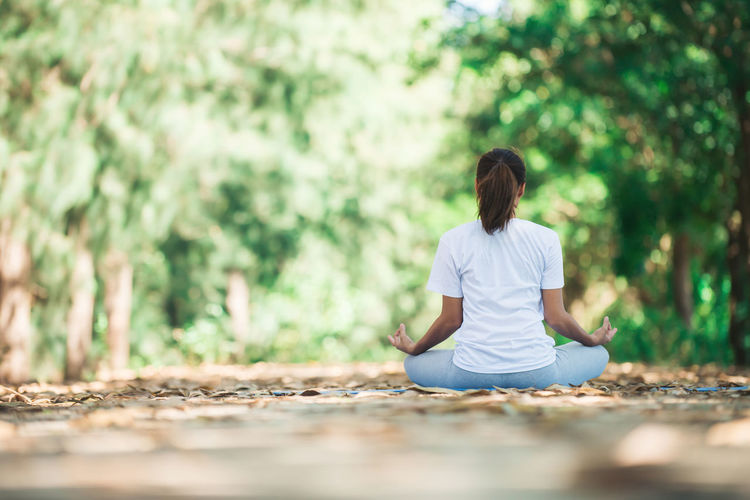 Rear view of young woman practicing yoga in lotus position at park