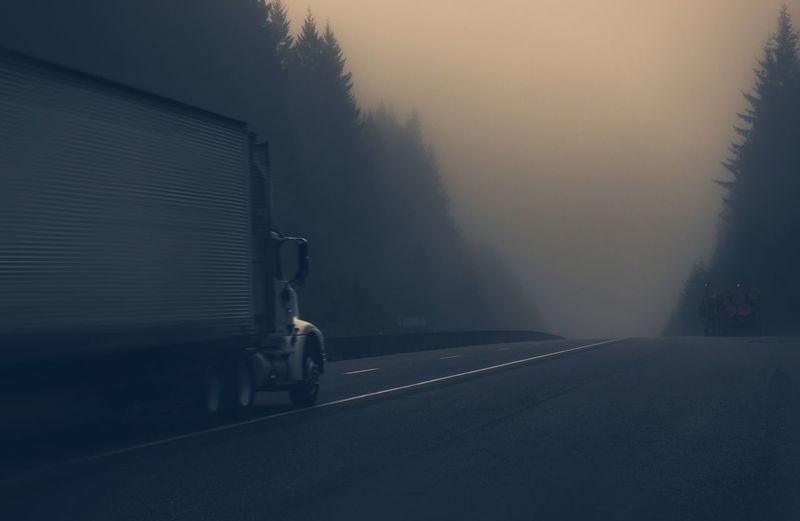 Truck on road during foggy weather