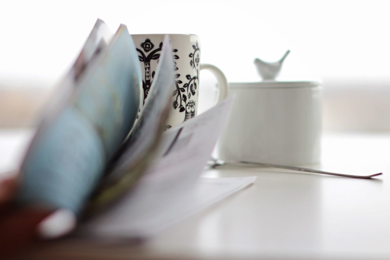 Close-up of book with coffee cup at home