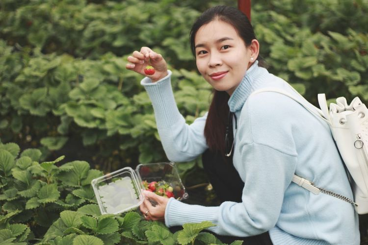 Portrait of smiling woman holding berry outdoors