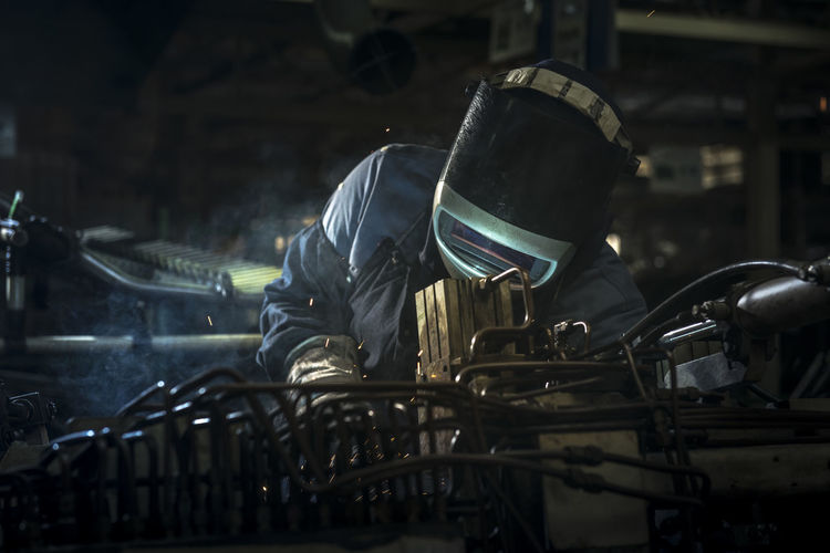 Worker Welding At Factory