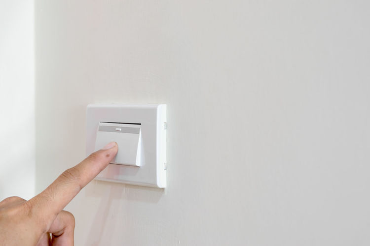 Cropped hand pressing button on wall at home