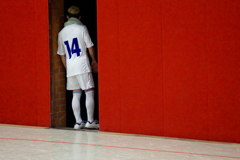 Rear view of sportsman standing on doorway amidst red wall