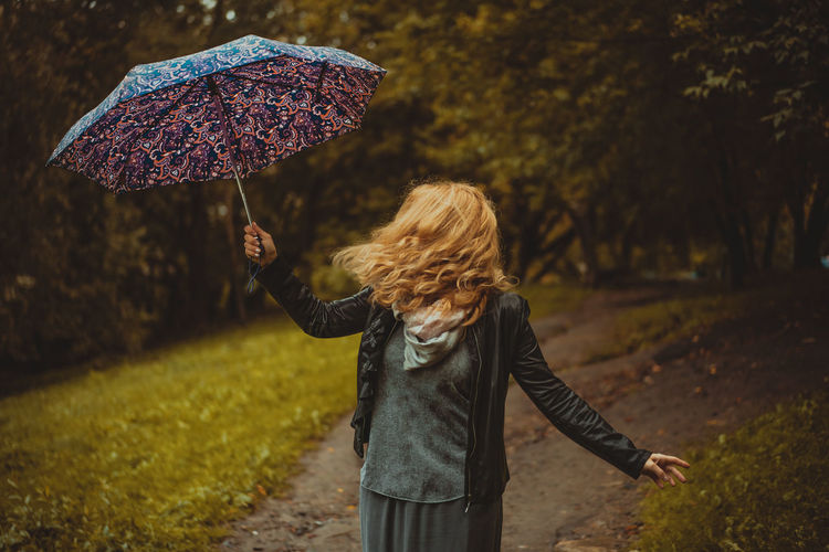 Woman With Umbrella On Footpath