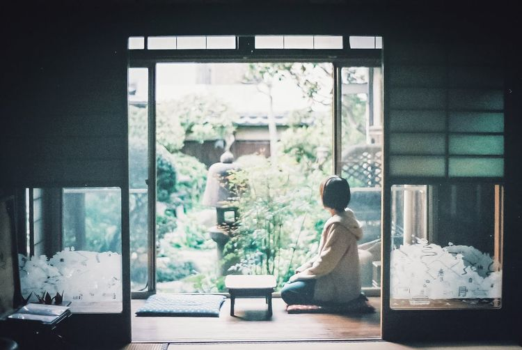 Side view of woman sitting in glass window