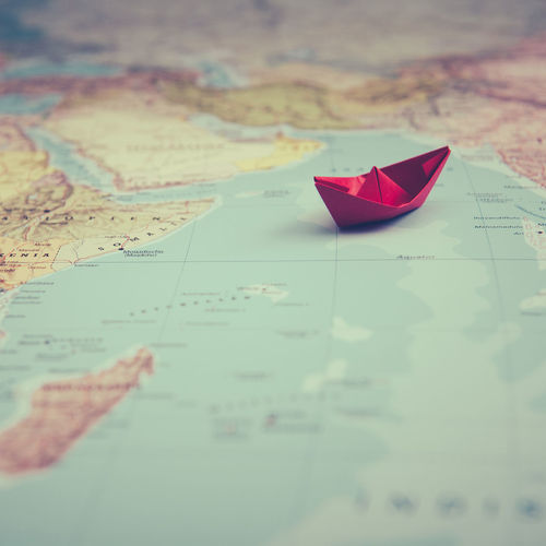Close-up of red paper boat on map
