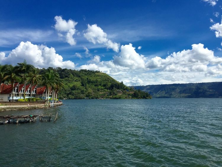 view of lake toba, one of 7 wonders in the world EyeEmNewHere Lake View LakeToba  INDONESIA Wonders Of The World EyeEm Selects Tree Water Sea Beach Blue Summer Relaxation Tourist Resort Beauty Sky