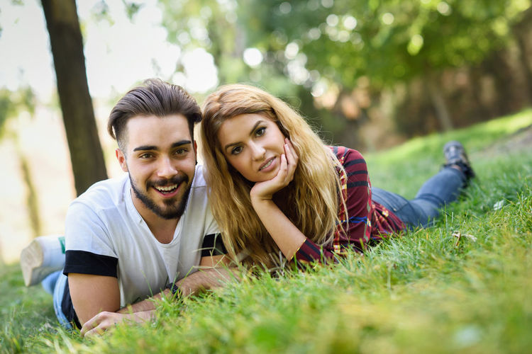 Beautiful young couple laying on grass in an urban park. Caucasian man and woman wearing casual clothes. Blonde female. Smiling Young Adult Happiness Portrait Togetherness Young Men Young Women Looking At Camera Two People Emotion Grass Plant Adult Lifestyles Casual Clothing Couple - Relationship Leisure Activity Men Real People Positive Emotion Young Couple Outdoors