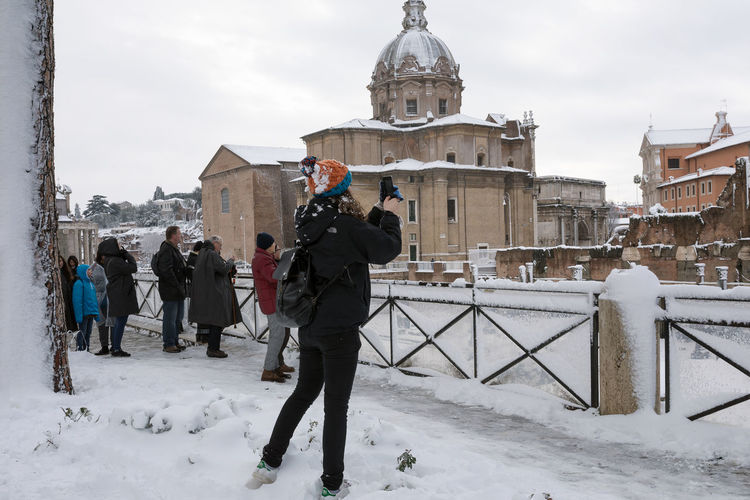 Snow covers the streets of Rome, Italy. Tourists and citizens photograph the event. Architecture Building Exterior Built Structure Cold Temperature Day Full Length Leisure Activity Men Nature One Person Outdoors People Real People Sky Snow Standing Travel Destinations Vacations Warm Clothing Weather Winter