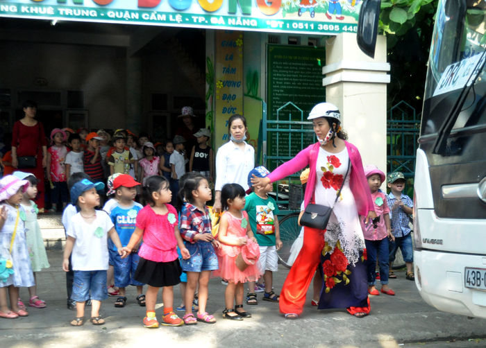Schoolchildren about to go on an outing in Da Nang, Vietnam. Ao Dai Banners Busses Children City Life Coaches Da Nang Education Gestures Handbags Helmets Holding Hands Lifestyles Outdoors Outings  Safety Schoolchildren Schools  Teachers Toddlers  Transport Vietnam Waiting The Color Of School