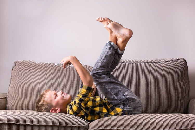 Boy lying on sofa at home