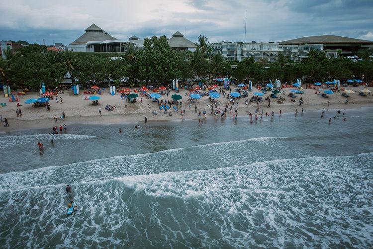 Group of people in swimming pool against sea