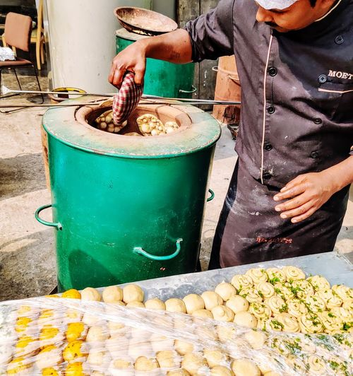 Midsection of man preparing food at market stall