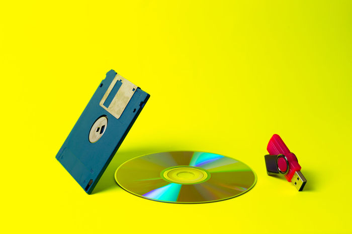 CDs Flashdrive  Old Meets New Old And New Technology Everywhere USB USB Flash Drive Close-up Day Diskette Multi Colored No People Passing Time Studio Shot Technology Yellow Yellow Background