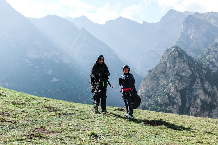 People on mountain top with paragliding equipment