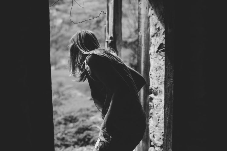 Side view of young woman looking outside