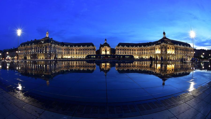 Illuminated castle reflection in water at place de la bourse against sky