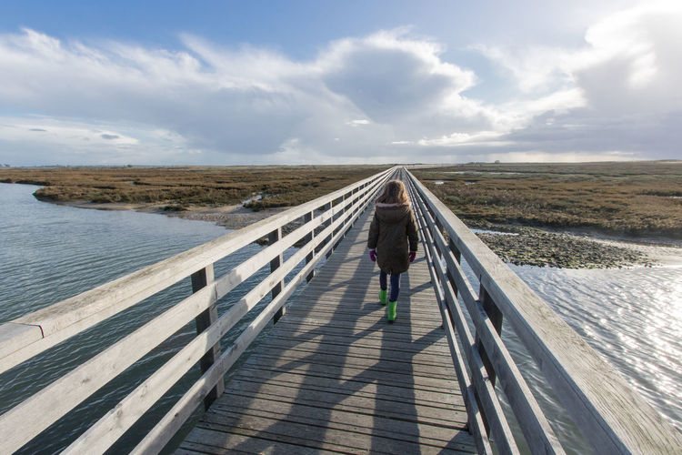 Rear view of girl walking on railing by river against sky