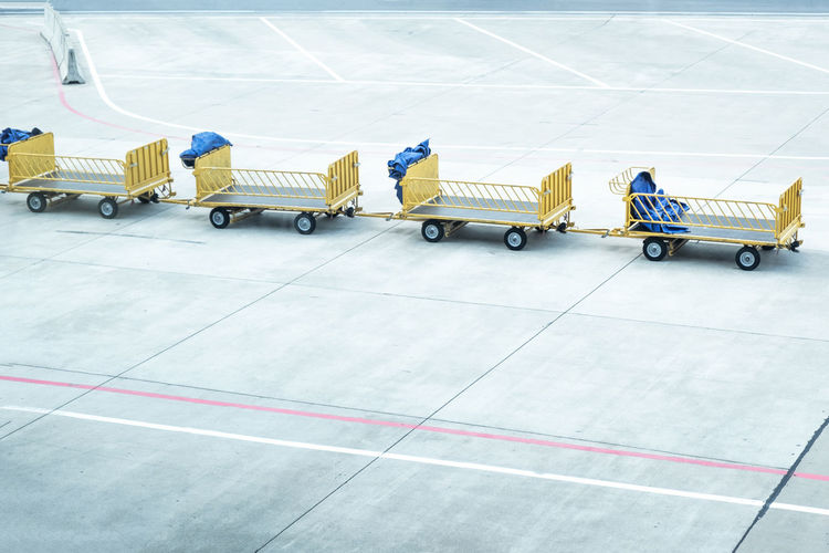 Copy Space In A Row Waiting Airport Airport Runway Concrete Consumerism Day Empty Flooring High Angle View Journey Land Vehicle Luggage Cart  Mode Of Transportation No People Outdoors Road Shopping Cart Sign Tile Tiled Floor Transportation Travel Yellow