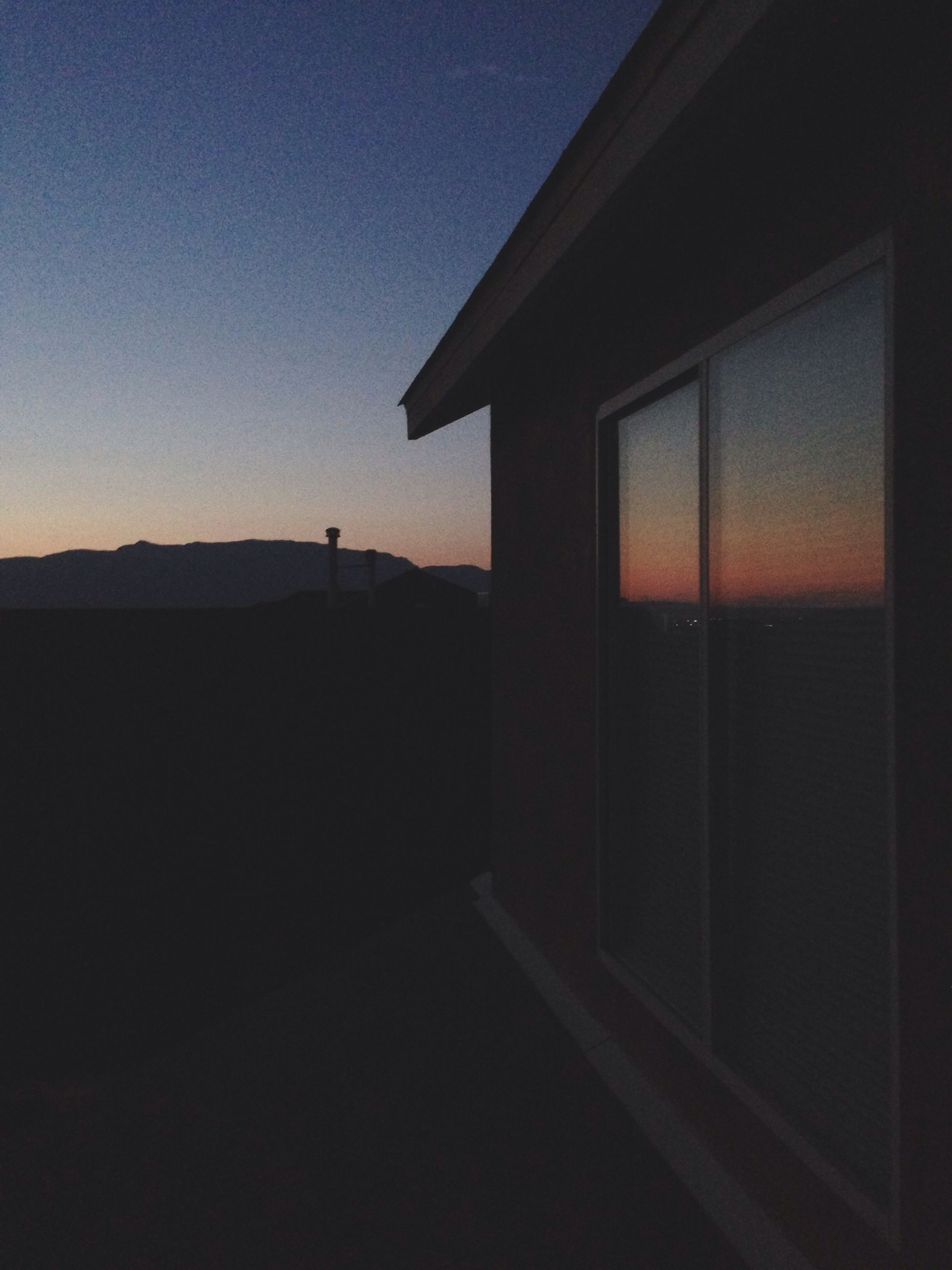 sunset, silhouette, built structure, architecture, copy space, sky, dark, clear sky, building exterior, dusk, sunlight, orange color, tranquility, no people, window, house, outdoors, nature, tranquil scene, illuminated