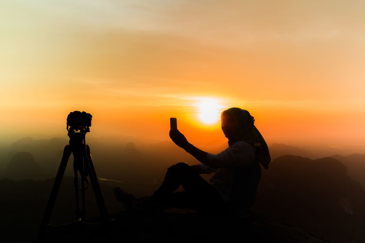 Silhouette woman taking selfie against orange sky