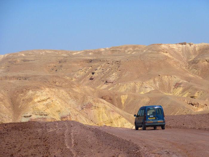 Car on desert against clear sky