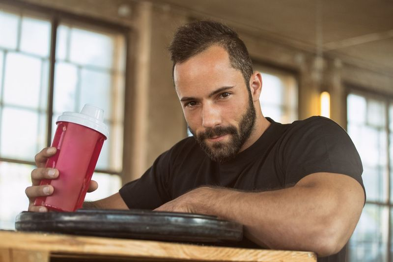 Portrait Of Handsome Bearded Man With Drink Bottle On Table