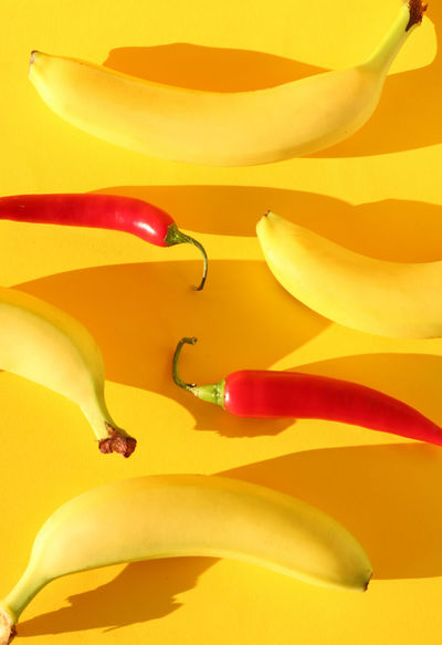 Abstract fruit pattern of real chillies and bananas on bright, colorful, yellow background Banana Bright Fun Natural Light Nature Abstract Background Chilli Close-up Color Clash Colorful Design Detail Food Photography Fresh Freshness Fruit Pattern Patterns Shadows Summer Texture Trendy Vegetable Yellow