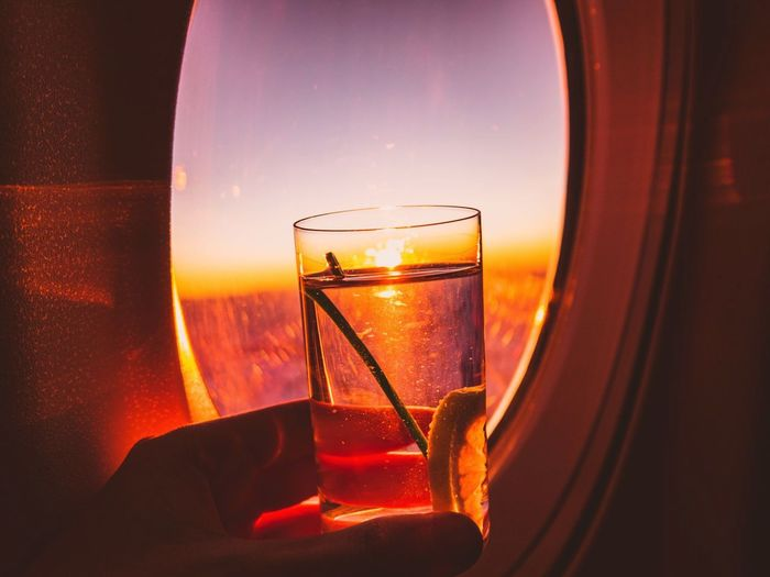 Cropped hand holding drink against airplane window