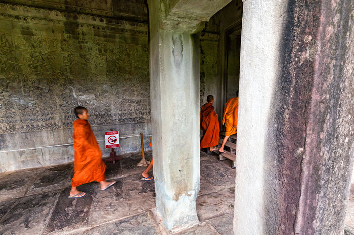 SIEM REAP - JUNE 11: Unidentified novice monks pass through arches in the main temple complex at Angkor Wat in Siem Reap, Cambodia on June 11, 2016. Angkor Thom Buddha Buddhist Cambodia Hindu Hinduism Khmer Culture Tourist Tourist Attraction  Travel UNESCO World Heritage Site Angkor Wat Apsara Buddhism Cambodian Khmer Khmer Empire Khmer Temple Monk  Monks Sculpture Southeast Asia Tourism Tourist Destination Unesco