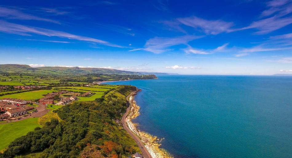 Aerial landscape shot of the coastal village of Cushendun found in the Northern Ireland with the big sea and the trees in the forest Water Scenics - Nature Sea Beauty In Nature Tranquil Scene Sky Tranquility Blue Land Cloud - Sky Beach Nature Day No People Idyllic Horizon Non-urban Scene Landscape Plant Outdoors Horizon Over Water Bay Ireland Cushendun North-Ireland East-Ireland Aerial View Tourism Green Travel Field