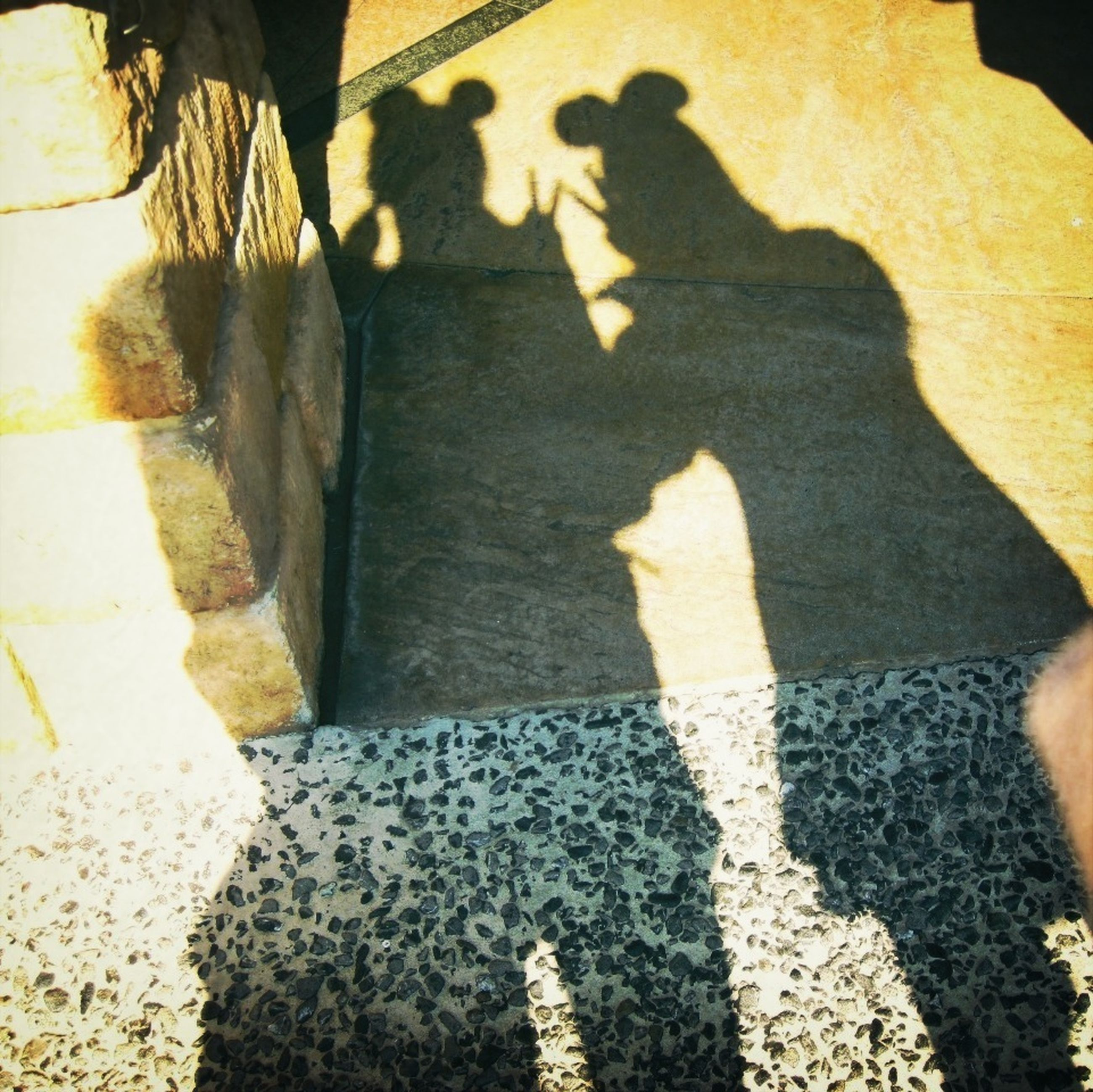 shadow, lifestyles, low section, men, high angle view, leisure activity, sunlight, togetherness, person, focus on shadow, standing, walking, street, unrecognizable person, bonding