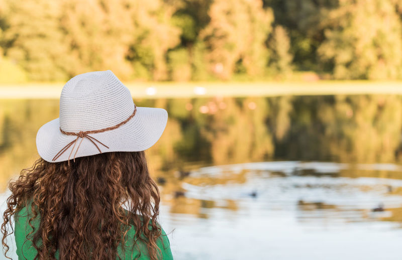 Rear view of woman wearing hat by lake