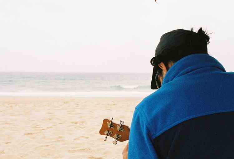Rear view of man playing guitar on beach
