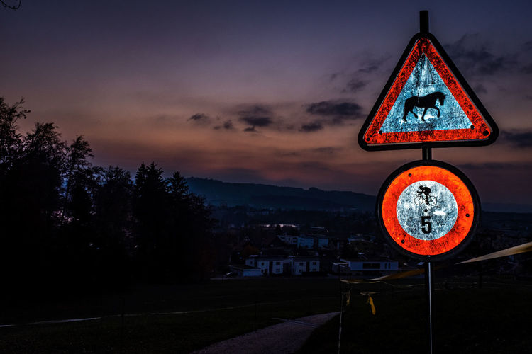 Sky Sign Communication Cloud - Sky Road Road Sign Sunset Warning Sign Architecture Nature City Built Structure Tree No People Guidance Illuminated Building Exterior Shape Transportation Night Outdoors