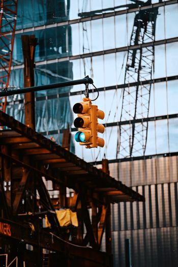 Low angle view of road signal hanging by building