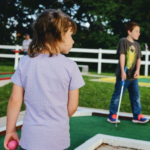 Rear View Of Girl With Brother Playing Miniature Golf At Lawn
