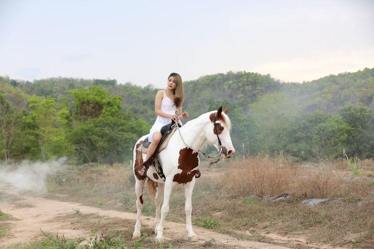 Full length of man riding horse on land