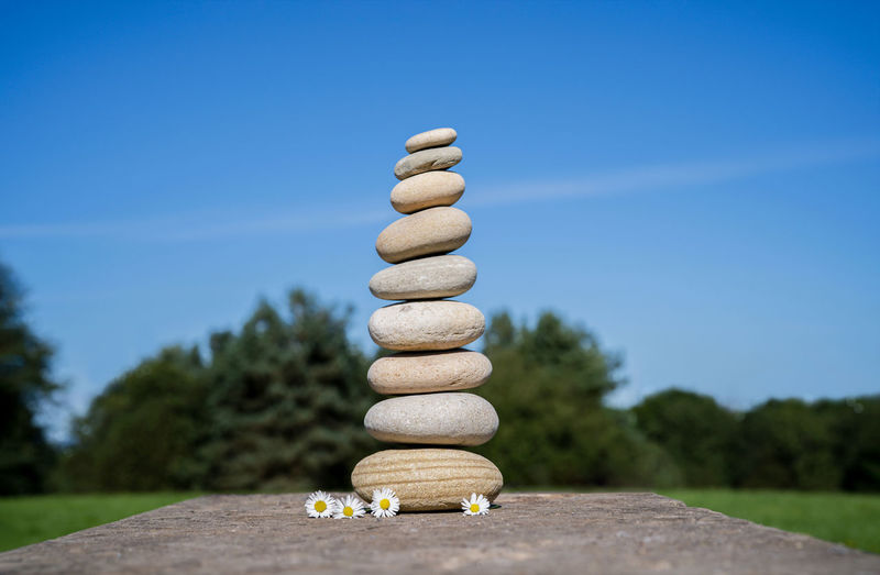 Stack of stones on table against blue sky
