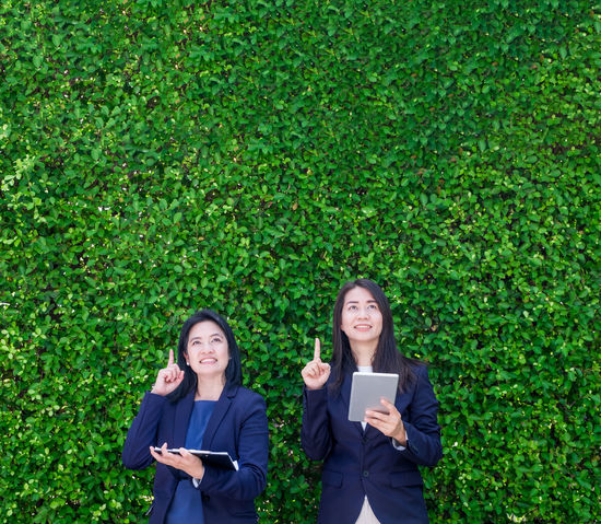 Two Asian businesswoman holding tablet and point finger up to air with thinking action at green leaf wall Business Copy Space Green Teamwork Thinking Businesswoman Communication Connection Ecology Female Finger Pointing Freshness Green Color Hedge Leadership Leaves Outdoors People Smiling Technology Two People Up Wireless Technology Women Working