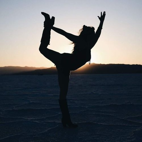 Silhouette woman stretching on salt flats against sky during sunset