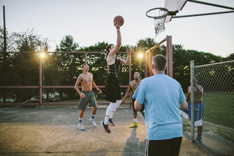 Men playing with basketball hoop against sky