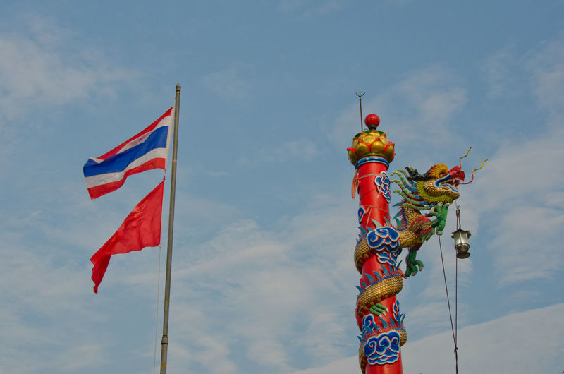 Low angle view of dragon statue on pole against thai flag