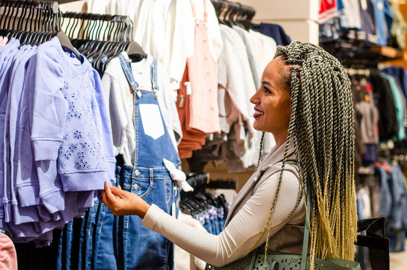 Side view of young woman standing in store