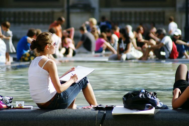 Woman Sitting At Swimming Pool And Writing In Book