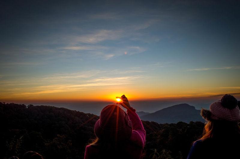 Optical illusion woman holding sun at sunset